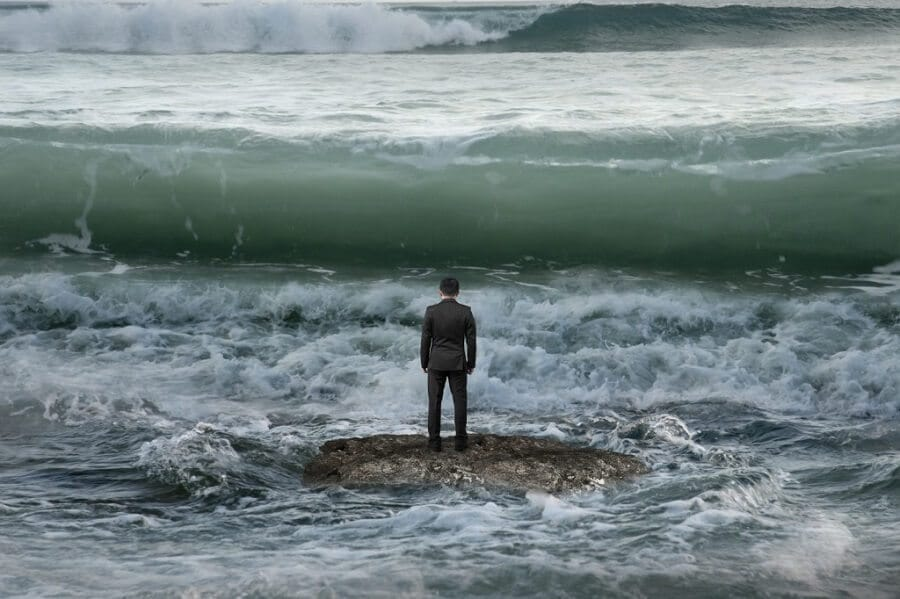 businessman standing on a rock in the sea