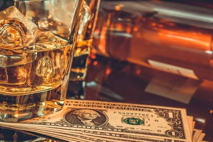 glasses of whiskey with ice and a stash of one dollar bills