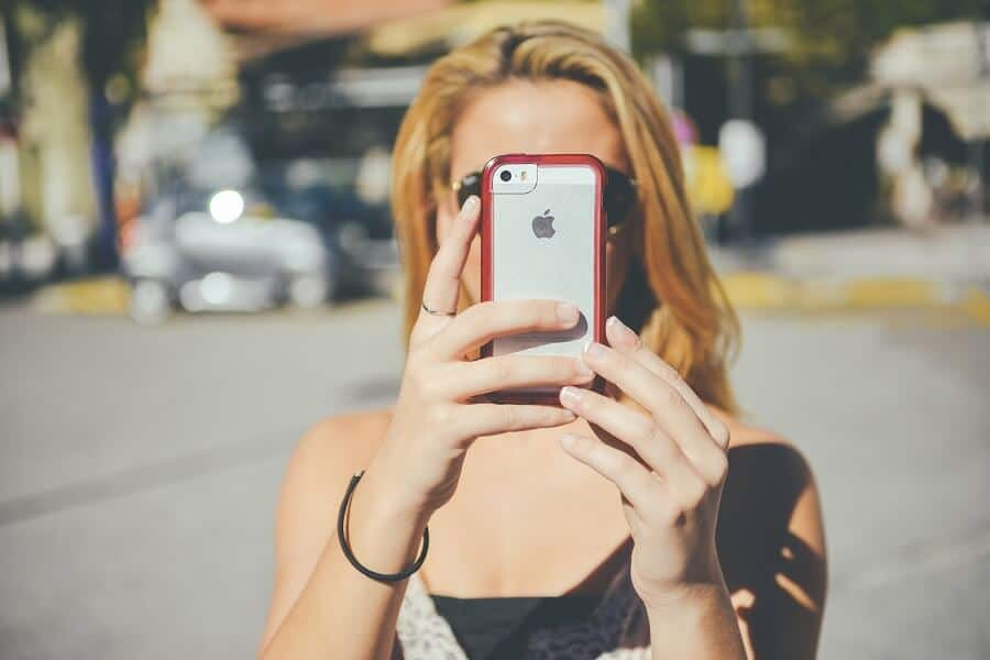 blonde woman taking a selfie in the street with an iphone
