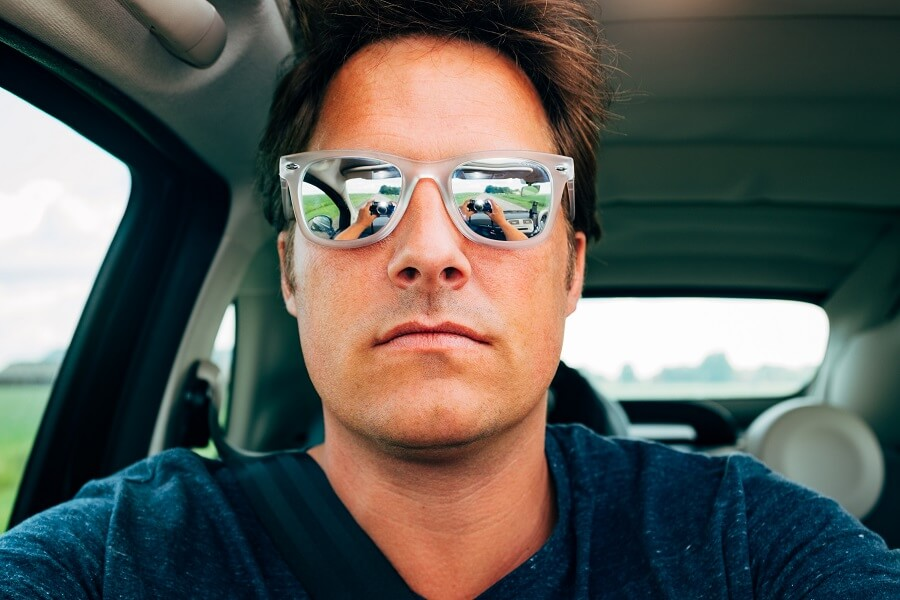 man taking selfie in car with sunglasses on