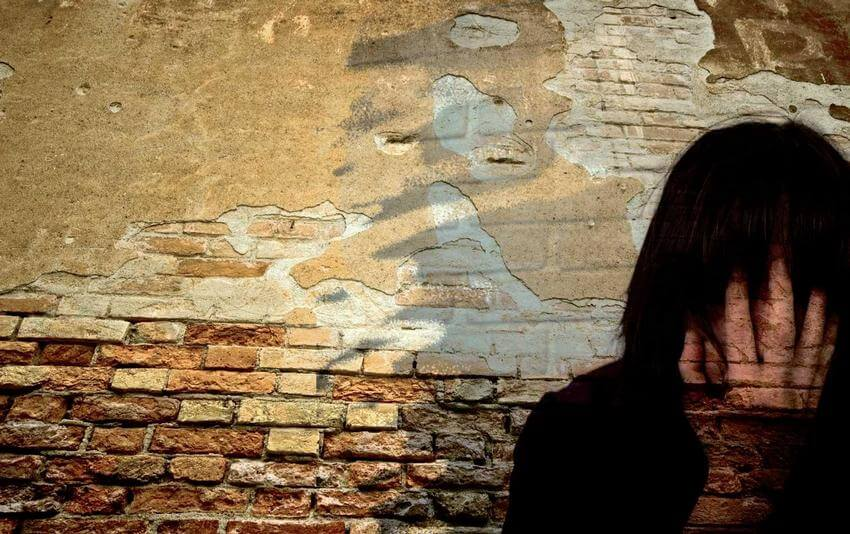 person with back against a brick wall and hand over face