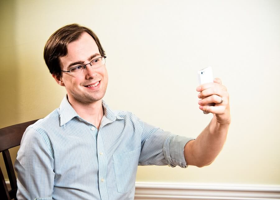 man with glasses smiling while taking a selfie