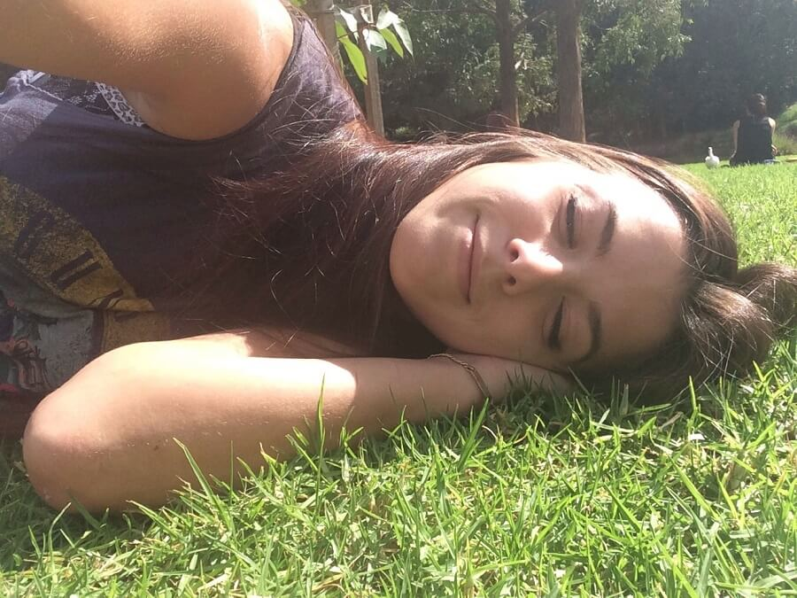 girl taking selfie while laying on the grass with eyes closed