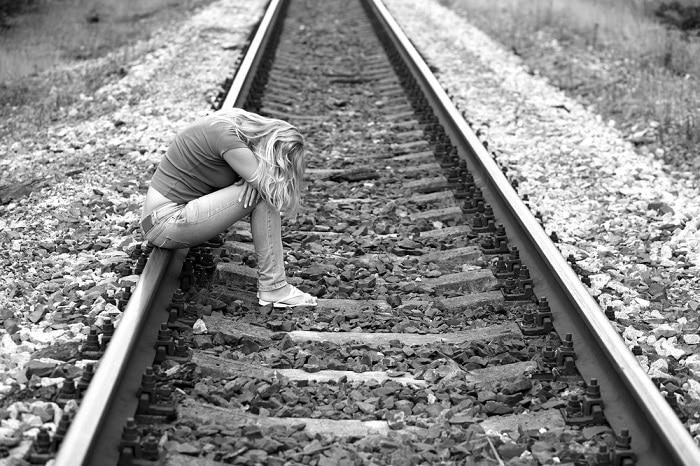 upset girl sitting on the rails